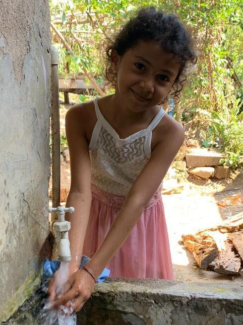 A girl smiles into the camera as she washes her hands under an outdoor faucet