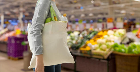 Shopper with reusable tote in grocery store