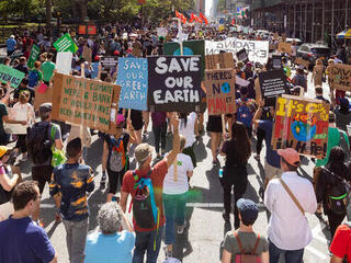 Marchers hold signs at New York City Climate March