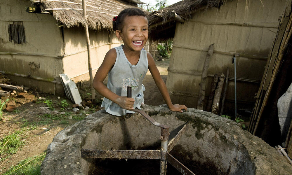 Surkhha Darai, age 5, turns the manure stirrer at her family home in the Bio-Gas Village.