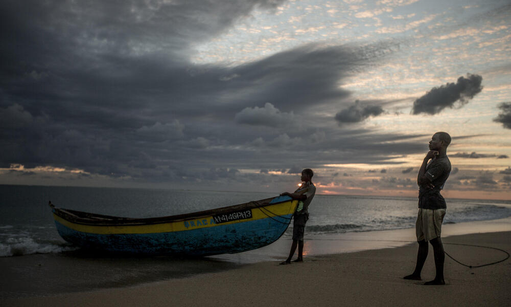 Two men with their boat on the beach in Mozambique