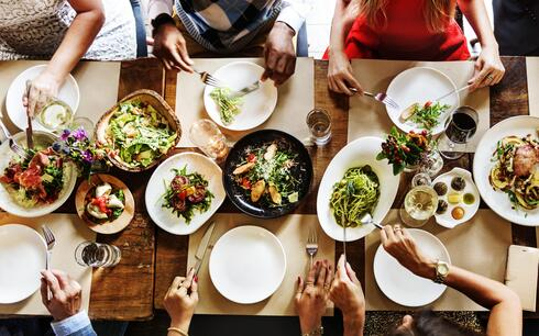 aerial shot of a group of people sitting around a table sharing a meal