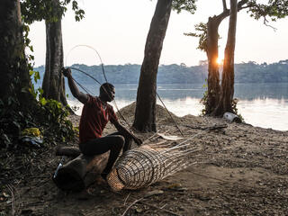 A man sitting on a riverbank weaving a fishing net out of reeds at sunset