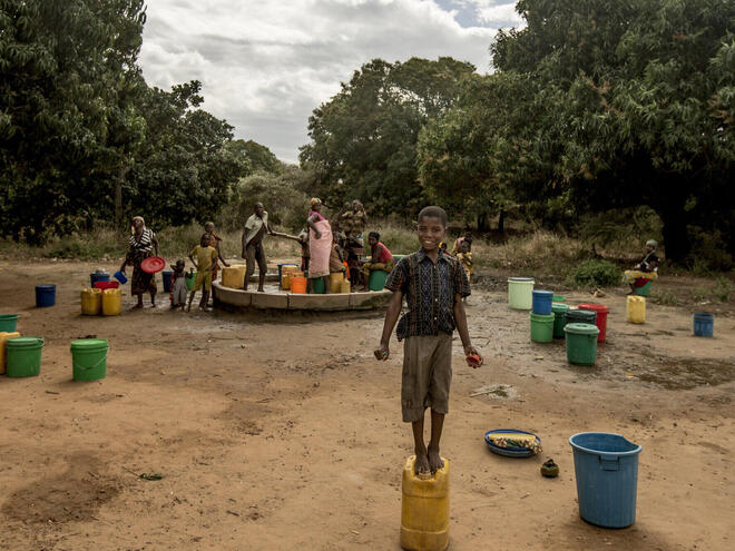 Boy stands on a container used for carrying water, with women gathering water in the background.