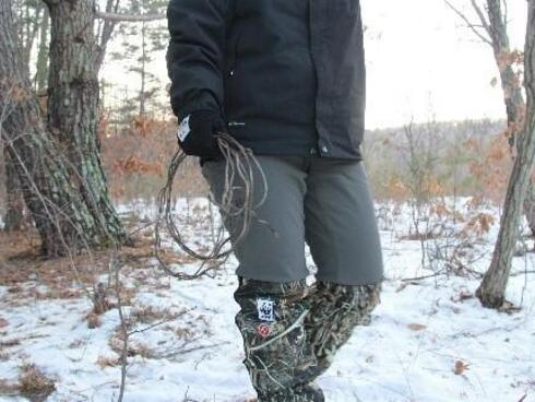 A ranger walks through the woods carrying a snare she's removed from the forest