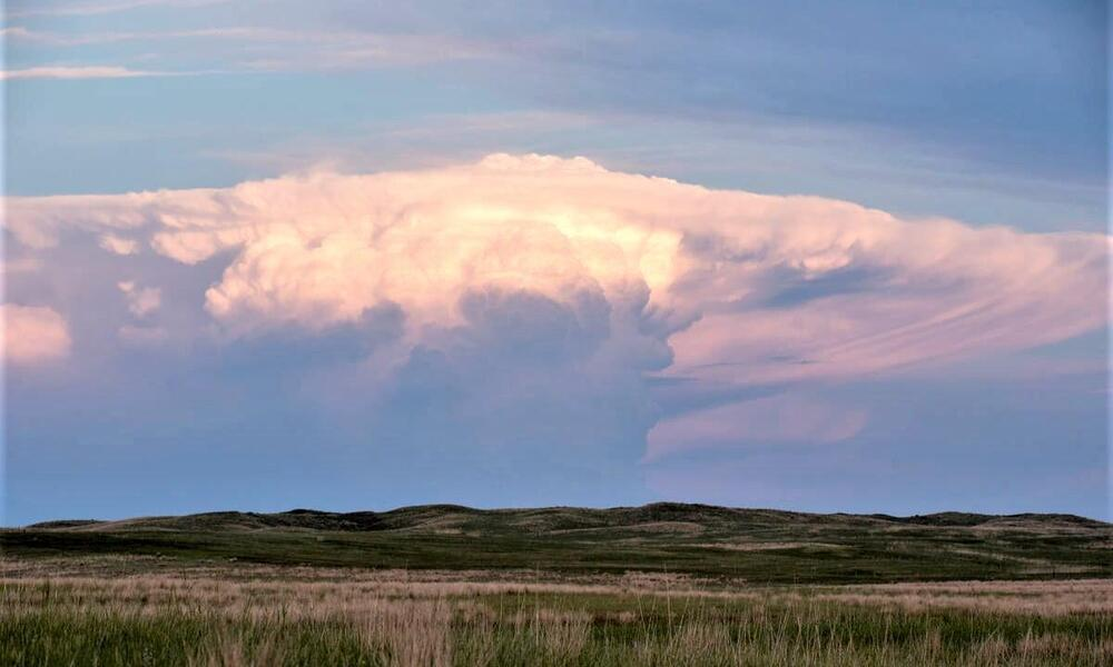 Wide landscape shot of a large storm cloud rolling over green grassland