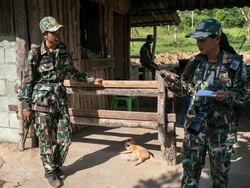 Woraya Makai (34) checks the GPS coordinates ahead of a morning patrol in the park.