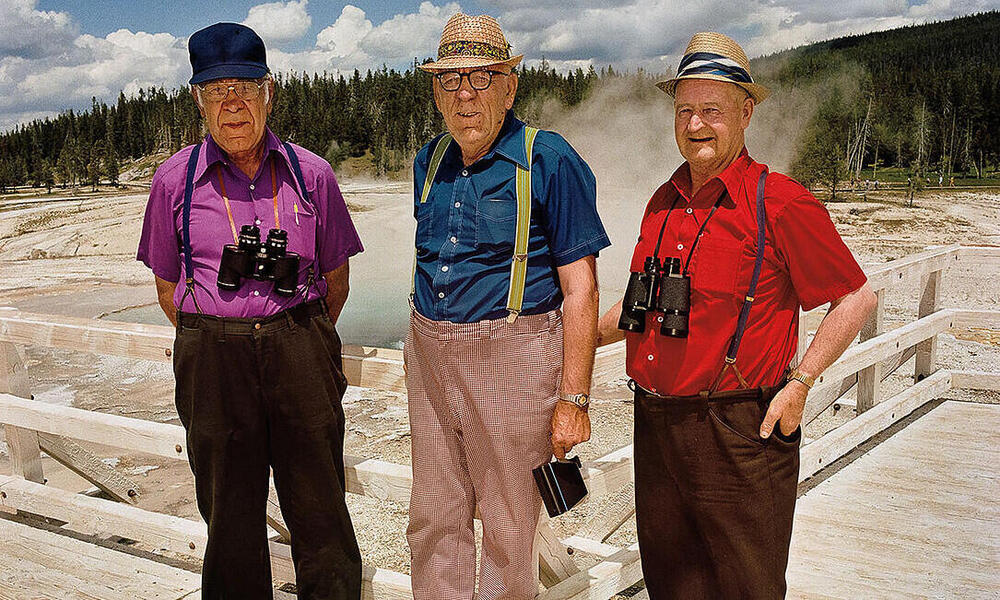 Three men pose for a photo in front of geysers