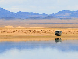 A camper van in the desert with mountains in the background