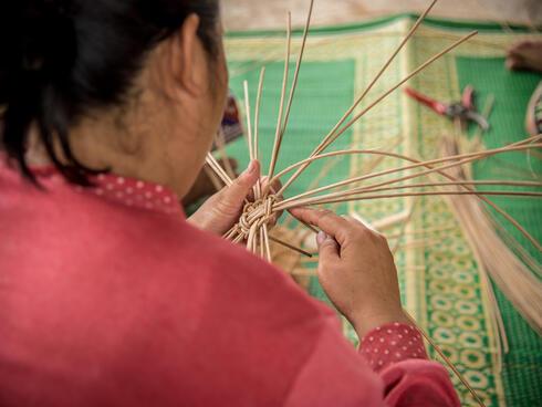 A woman basket weaving.