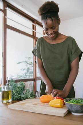 A woman stands in a kitchen chopping peppers