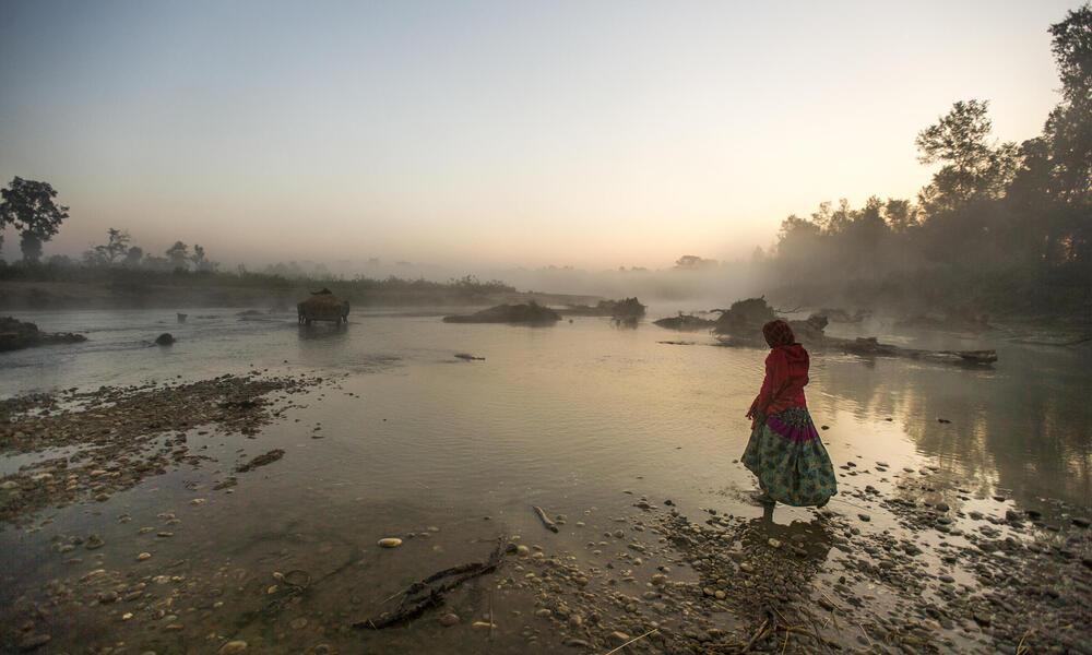 Woman walking through lake in Nepal