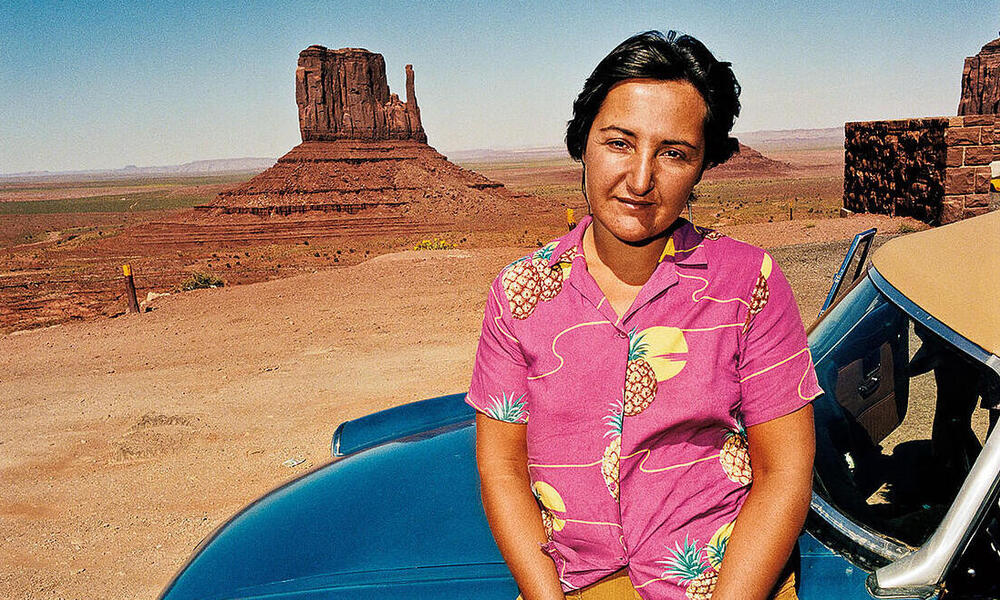 A woman poses in front of The Mittens in Navajo County, Arizona