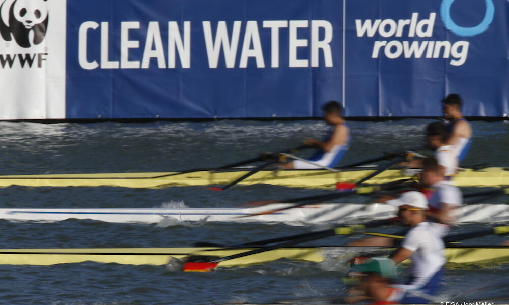 Rowers with partners for clean water sign in the background.