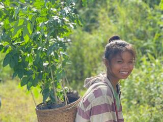 Young girl carrying seedling on her back and smiling in Laos