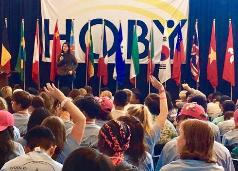 A woman standing on a stage in front of a row of flags, presenting to an audience of children with their hands up